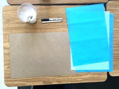 Tables ready with a light cardboard, tissue paper, glue and a brush, a sharpie and a pencil.