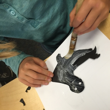 The student glue the shape of their animal on a piece of velum