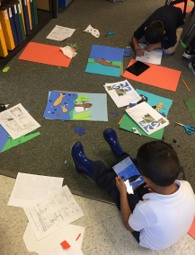 Students working on their poster - paper cut composition and using iPads to take a photo and add the text.